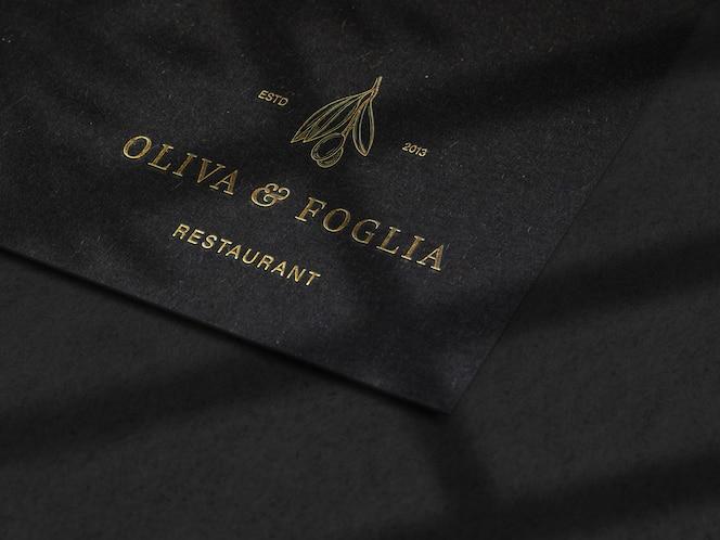 maqueta de logotipo en relieve de lujo sobre textura de papel negro