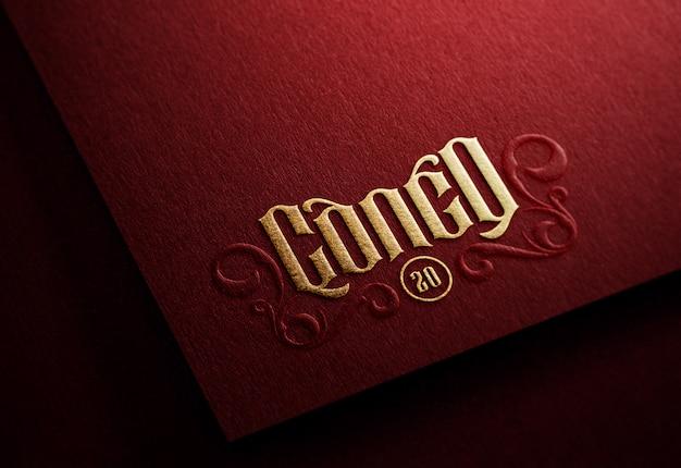 Maqueta de logotipo sobre papel oscuro con efecto dorado en relieve