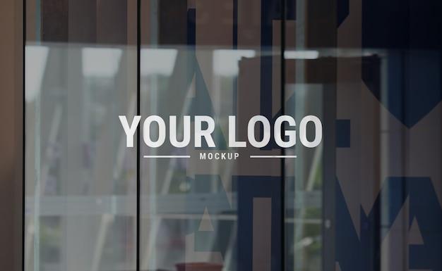 Maqueta de logotipo sobre vidrio en centro comercial