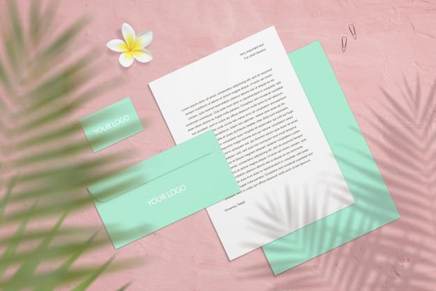 Maqueta de marca con tarjetas de visita, carta con flores y sombras de palmeras