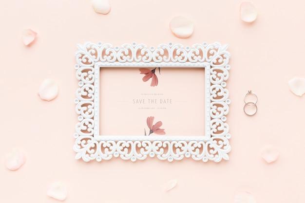 Maqueta de marco y anillos de boda con flores.