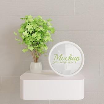 Maqueta de marco blanco circular en escritorio de pared con planta decorativa