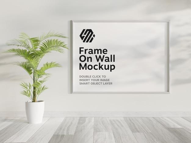 Maqueta de marco blanco colgado en la pared