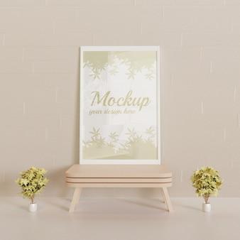 Maqueta de marco blanco de pie sobre la mini mesa de madera con un par de plantas decorativas