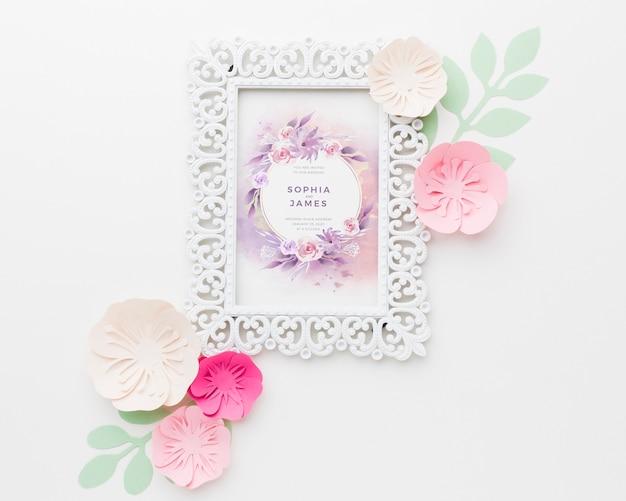 Maqueta de marco de boda con flores de papel sobre fondo blanco.