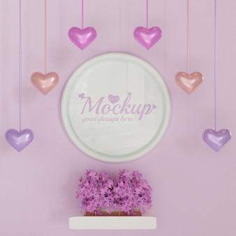 Maqueta de marco de círculo blanco en pared rosa con plantas de hojas rosadas y decoración colgante en forma de corazón