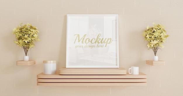 Maqueta de marco cuadrado blanco de pie sobre el escritorio de pared de madera con plantas decorativas