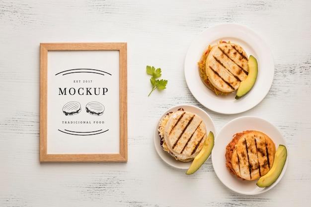Maqueta de marco y deliciosos sándwiches planos.