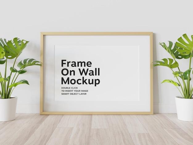 Maqueta de marco dorado apoyado en la pared