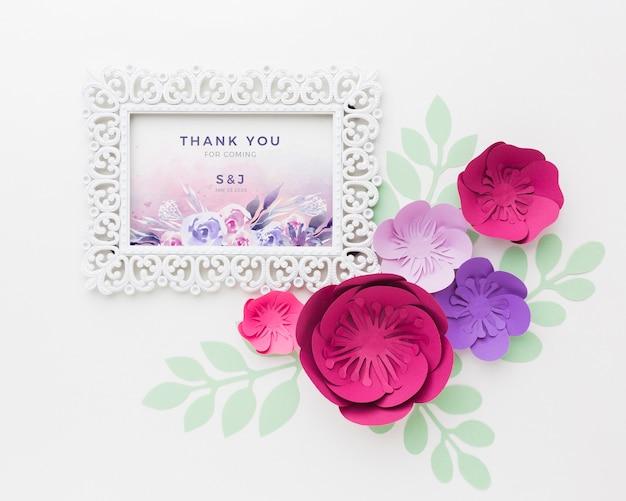 Maqueta de marco con flores de papel sobre fondo blanco.