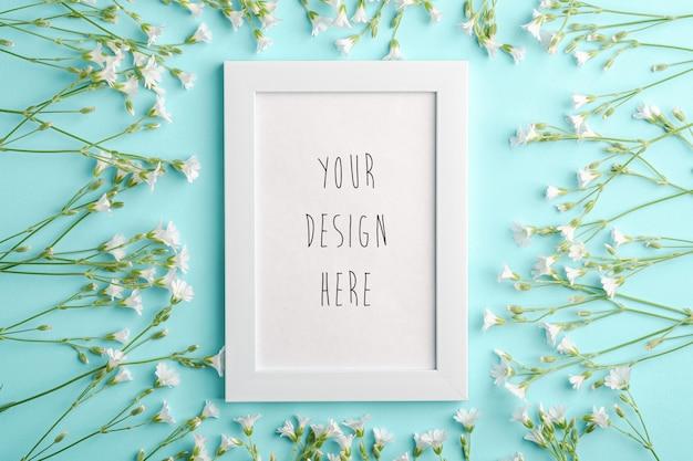 Maqueta de marco de fotos vacío blanco con flores de pamplina