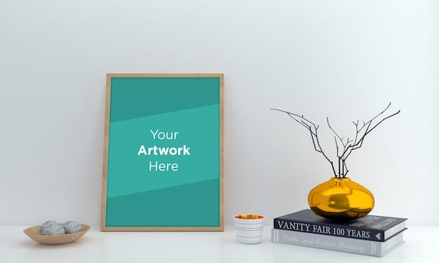 Maqueta de marco de fotos vacío con libros y florero dorado
