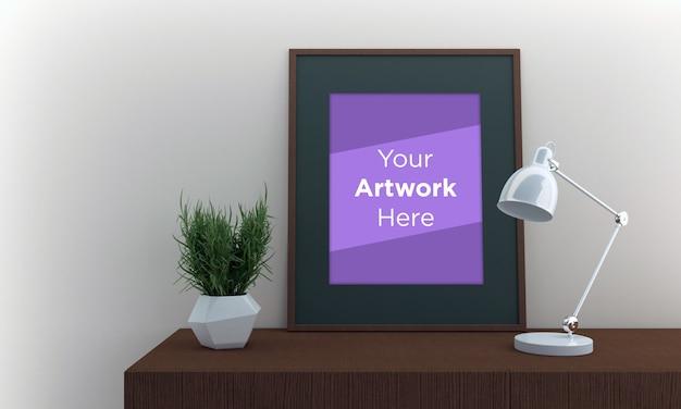 Maqueta de marco de fotos vacío tendido en el gabinete con lámpara