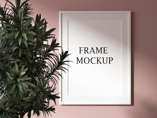 Maqueta de marco de imagen blanco al lado de la planta