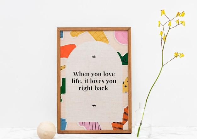 Maqueta de marco de imagen de madera psd con cita motivacional sobre fondo de collage de papel rasgado