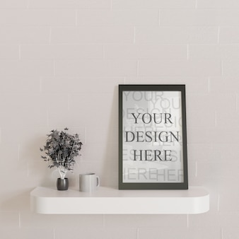 Maqueta de marco negro horizontal con plantas decorativas en el escritorio de pared blanca