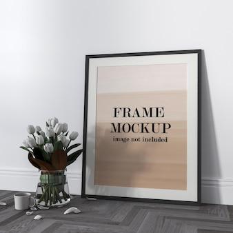 Maqueta de marco de póster al lado de flores blancas