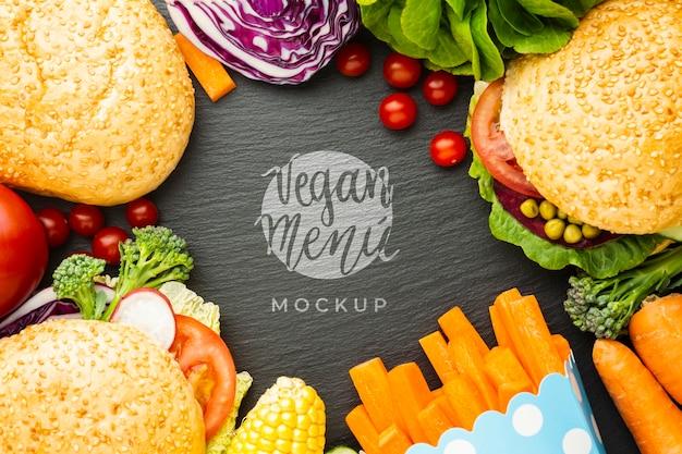 Maqueta de menú vegano rodeada de bollos y verduras