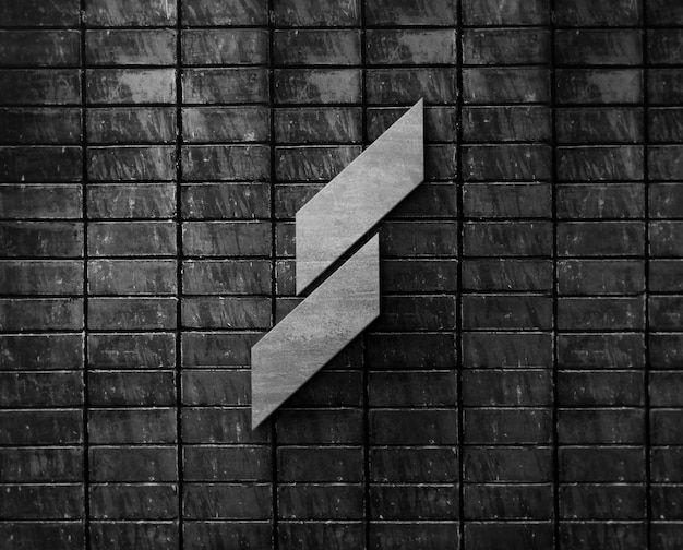 Maqueta de metal con logotipo 3d en pared de ladrillo negro