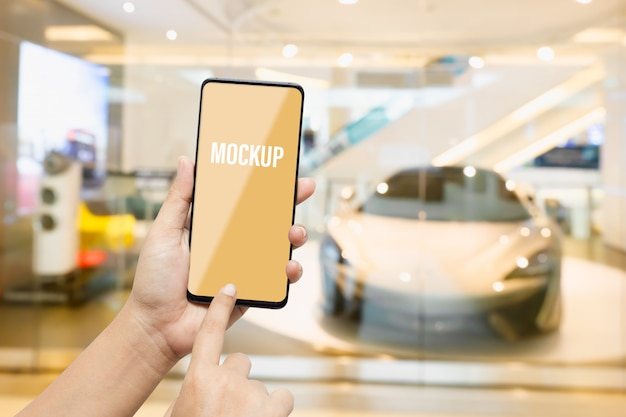 Maqueta móvil de pantalla en blanco con fondo borroso de pantalla de coches nuevos en sala de exposición