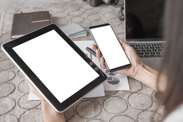 Maqueta de mujer de negocios de cerca que trabaja con la tableta del teléfono inteligente y documentos en la oficina