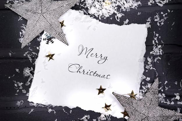 Maqueta navideña con tarjeta, estrellas plateadas y ramas de abeto