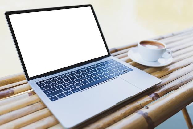 Maqueta del ordenador portátil y café caliente en una taza de café con leche en una mesa de bambú, al aire libre