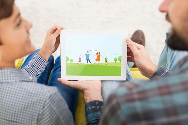 Maqueta padre e hijo mirando en tableta