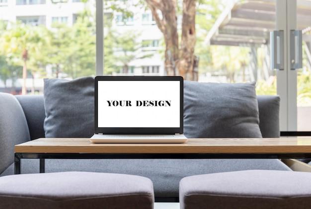 Maqueta pantalla en blanco del portátil en la mesa de madera.