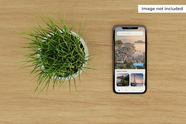 Maqueta de pantalla de dispositivo móvil realista con planta