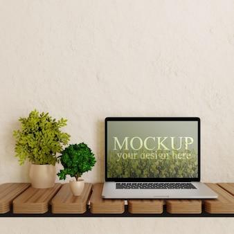 Maqueta de la pantalla del portátil en el escritorio de pared de madera con plantas