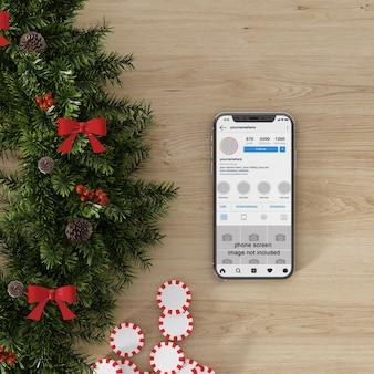Maqueta de pantalla de smartphone junto a decoración navideña