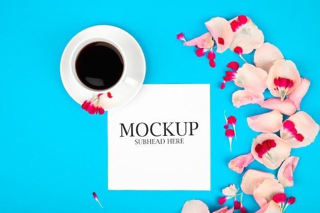 Maqueta de papel blanco taza de café y flores rosas sobre un fondo azul.
