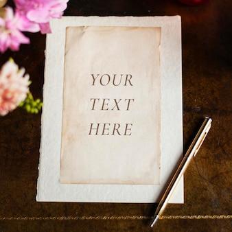Maqueta de papel vintage en una mesa de madera con flores