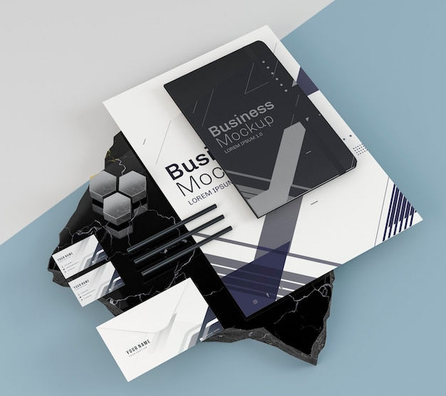 Maqueta de papelería empresarial y cuaderno negro