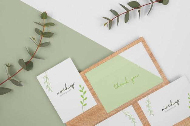 Maqueta de papelería con hojas y madera.