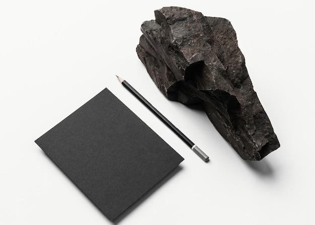 Maqueta de papelería con piedra oscura.