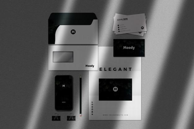 Maqueta de papelería realista con teléfono y tarjetas de visita.