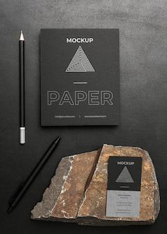 Maqueta de papelería sobre hormigón oscuro con roca rugosa