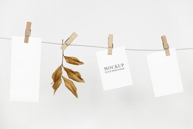Maqueta de papeles psd colgando de una cuerda con clips de papel