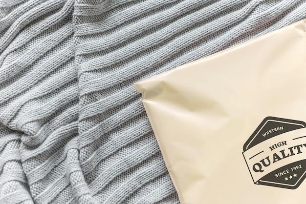 Maqueta de paquete de plástico en una cama