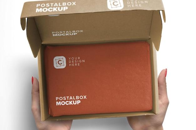 Maqueta de paquete de primer plano con manos de mujer sosteniendo buzón postal abierto