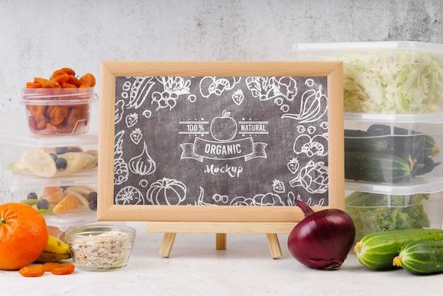 Maqueta de pizarra con alimentos orgánicos.