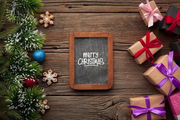 Maqueta de pizarra y regalos con hojas de pino de navidad