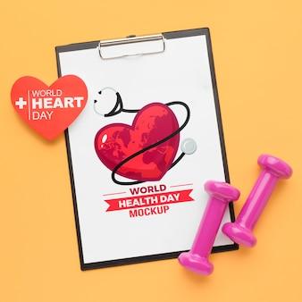 Maqueta plana del día de la salud y pesas rosas