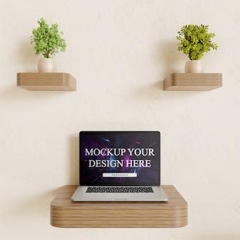 Maqueta del portátil en el escritorio de pared con decoración de plantas par