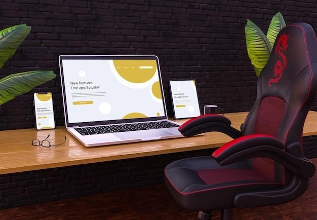 Maqueta de portátil móvil y tableta en mesa y silla de madera