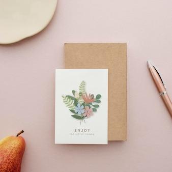 Maqueta de postal floral sobre una superficie rosa