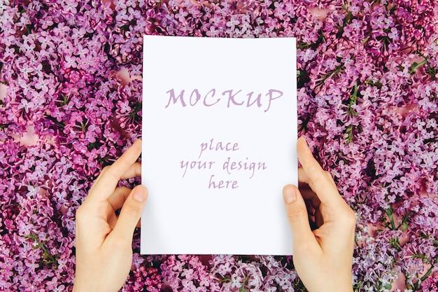 Maqueta con una postal en manos de las mujeres sobre un fondo rosa con ramas de flores lilas