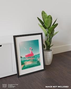 Maqueta de póster de marco de arte apoyado contra el armario blanco